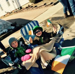 Two young children, bundled in winter clothing, watch as the Irish Parade goes by.