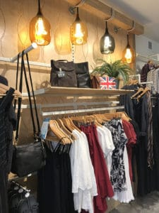 Women's shirts and tank tops in white, black, and red are displayed below large light fitures.
